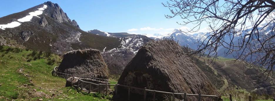 Dos teitos de Teverga en primer plano con montañas al fondo. Brañas de Teverga
